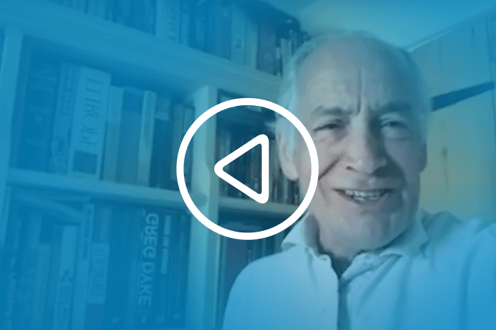 A play button graphic featuring friend of the University Alastair Stewart