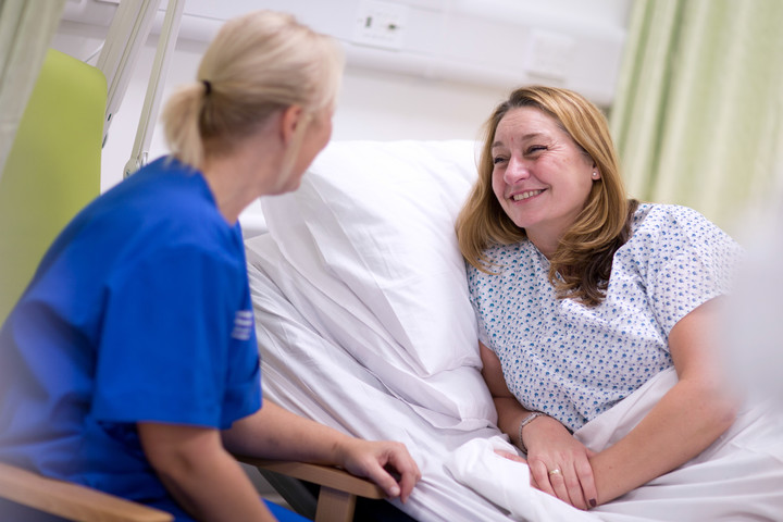 Nurse talking to a patient in bed.