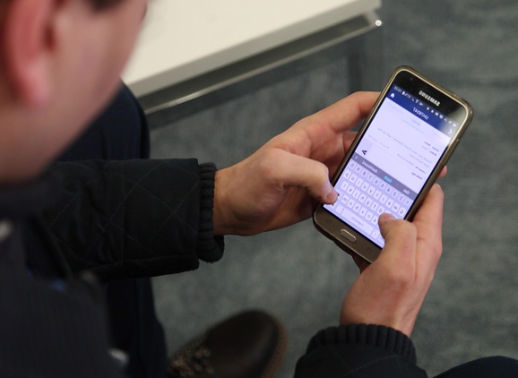 A male student using a smartphone